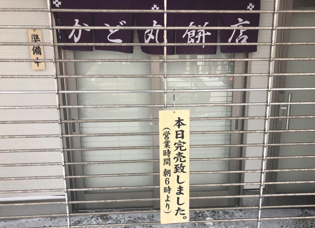 かど丸餅店のシャッターが閉まったの前の本日の完売の看板
