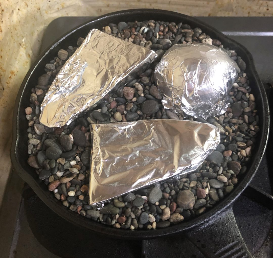 スキレットに石を敷き詰めたところにアルミ箔で包んだ芋はを入れた
