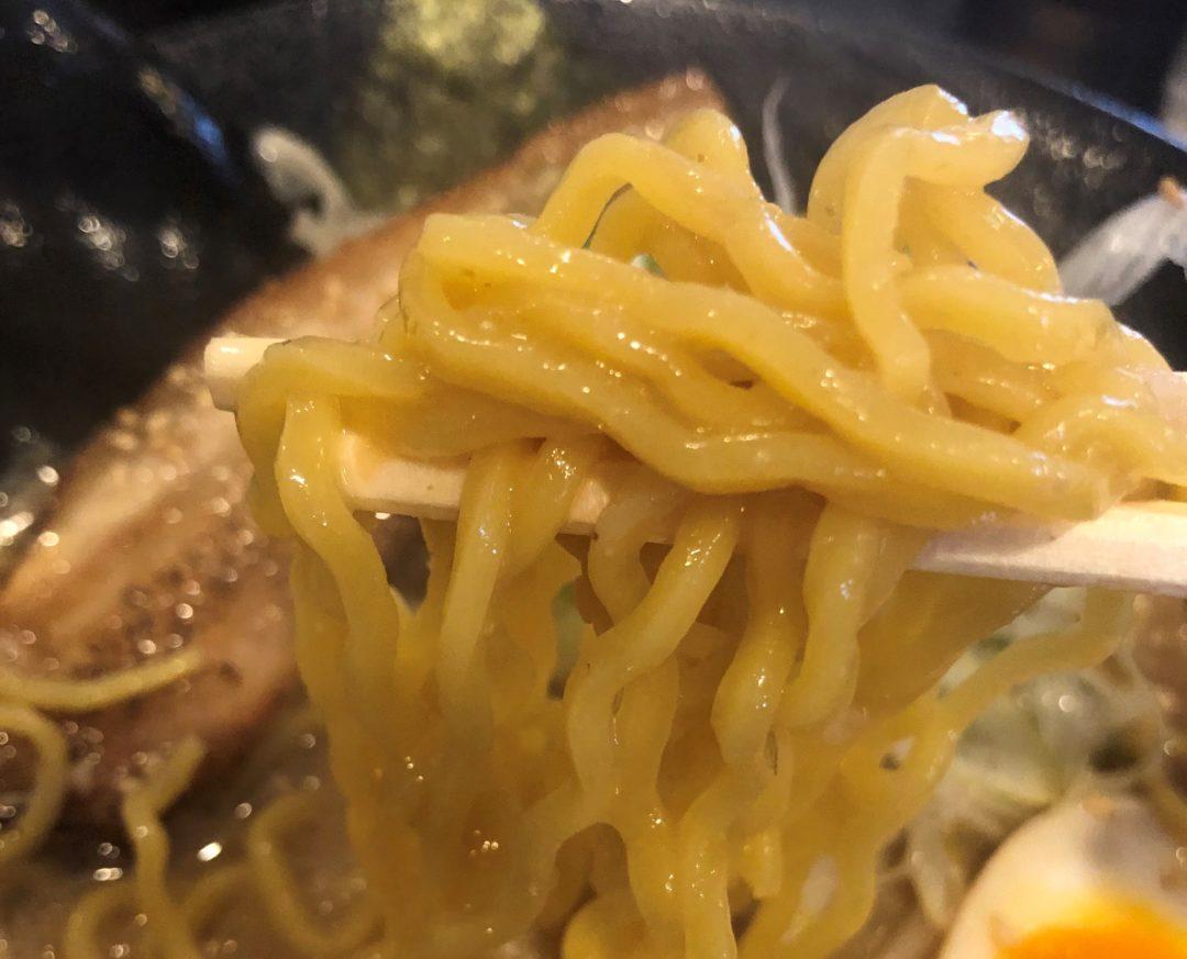 箸で持ったラーメンの麺