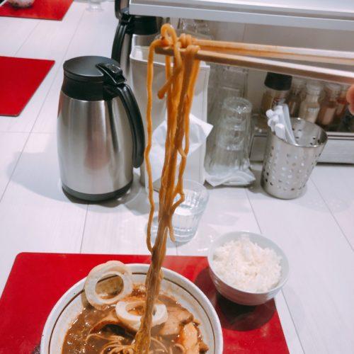 丸ふの長い麺を箸で持って上に上げる