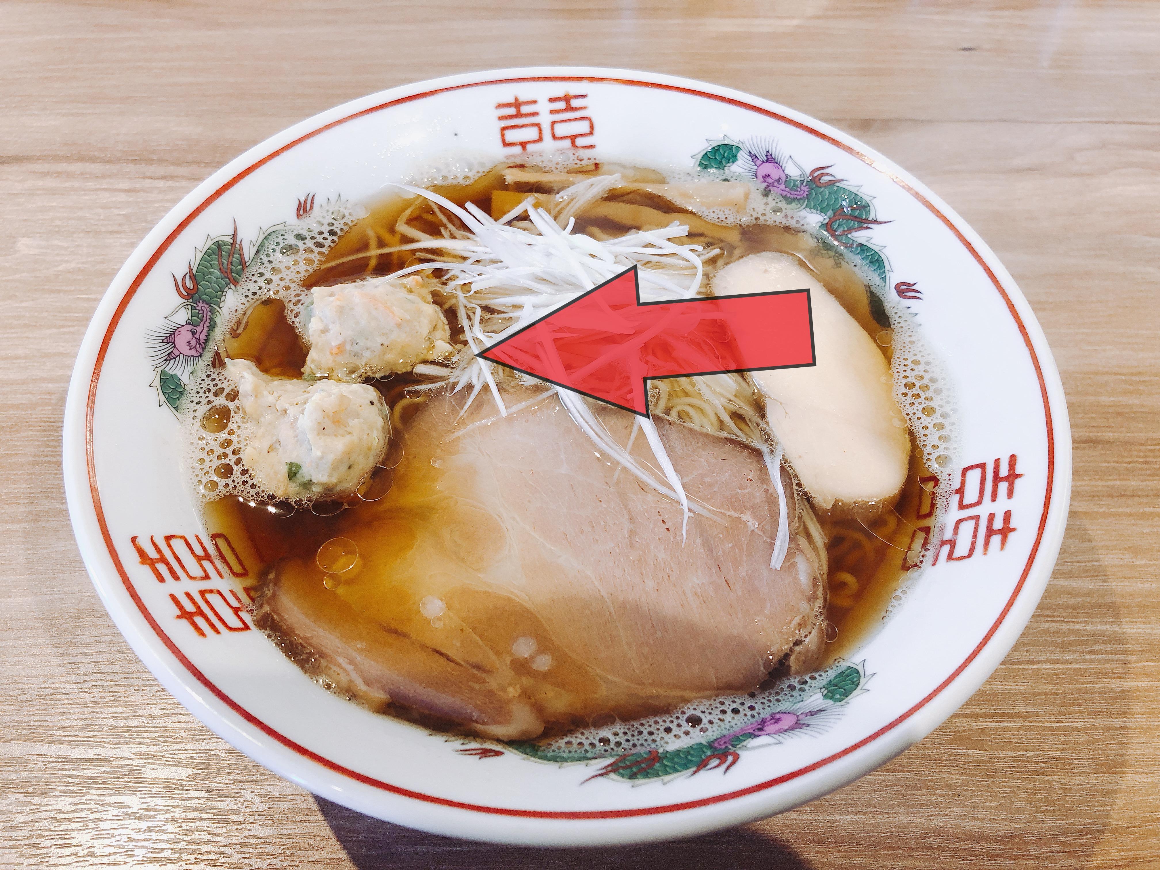 木蓮の焼あご出汁醤油ラーメンの肉団子を赤矢印で指している