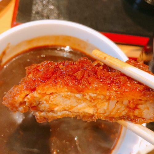 帯広 ぶた一家のとんかつ一切れを味噌ダレにどっぷり付けて箸で持った
