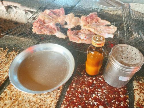 鶏肉の半身を炭火で網焼きの横にアルミ皿と塩コショウ
