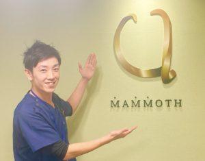 マンモス脱毛の代表がマンモス脱毛のロゴを手を広げて指している様子