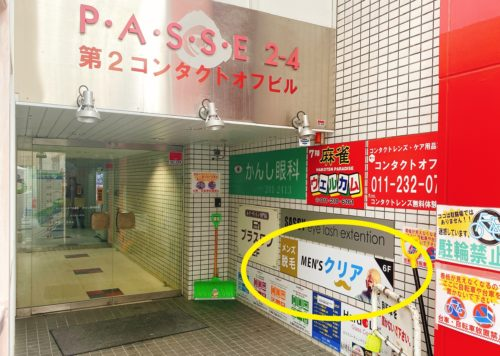 メンズクリア北海道札幌店の入っている第2コンタクトオフビルの壁にメンズクリアの看板を○