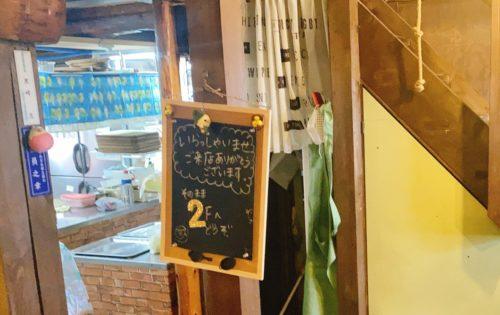 うまごやカフェの2階に上がる看板とその裏に階段